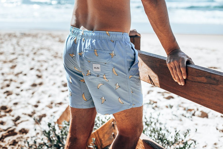 Close up shot of Eubi board shorts. Bananas printed on baby blue solid background