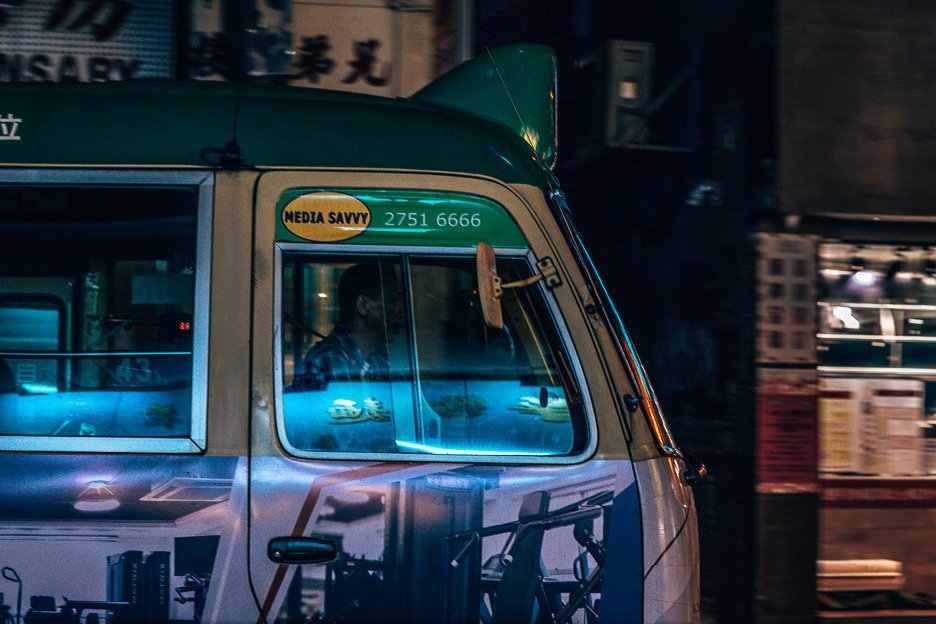 A driver of a public light bus in the shadows, Mong Kok, Hong Kong