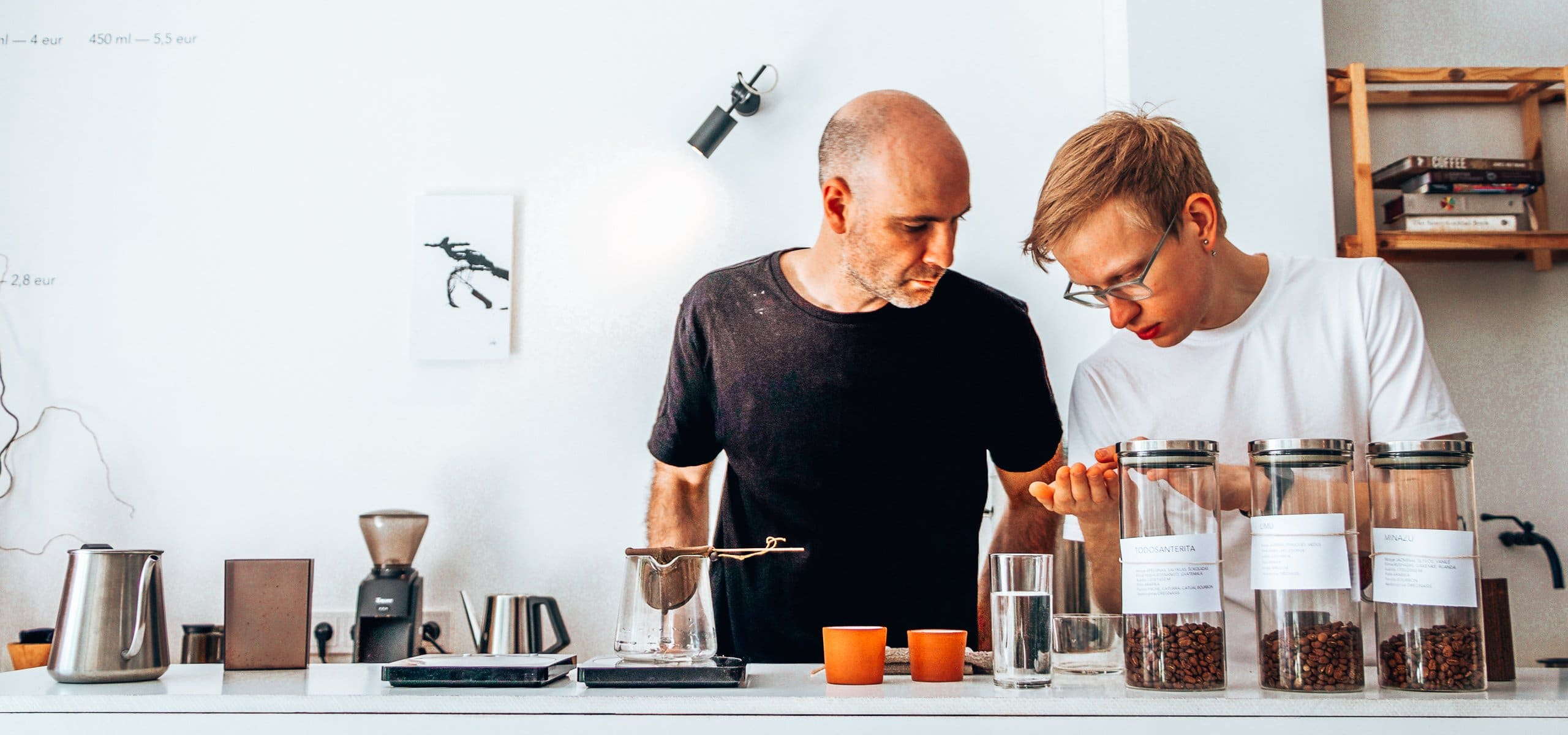 Baristas examine coffee beans at the coffee counter of Crooked Nose & Coffee Stories in Vilnius, Lithuania