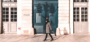 Jasmine walks past an impressive door in Place Vendome, Paris