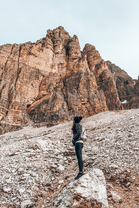 Jasmine stands on a rock looking up at the peaks of Tre Cime di Lavaredo in The Dolomites, Italy
