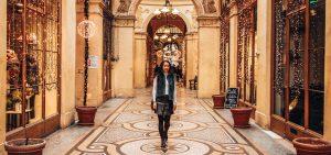 Jasmine walks through a mosaic corrider in Galerie Vivienne under fairylights, Paris