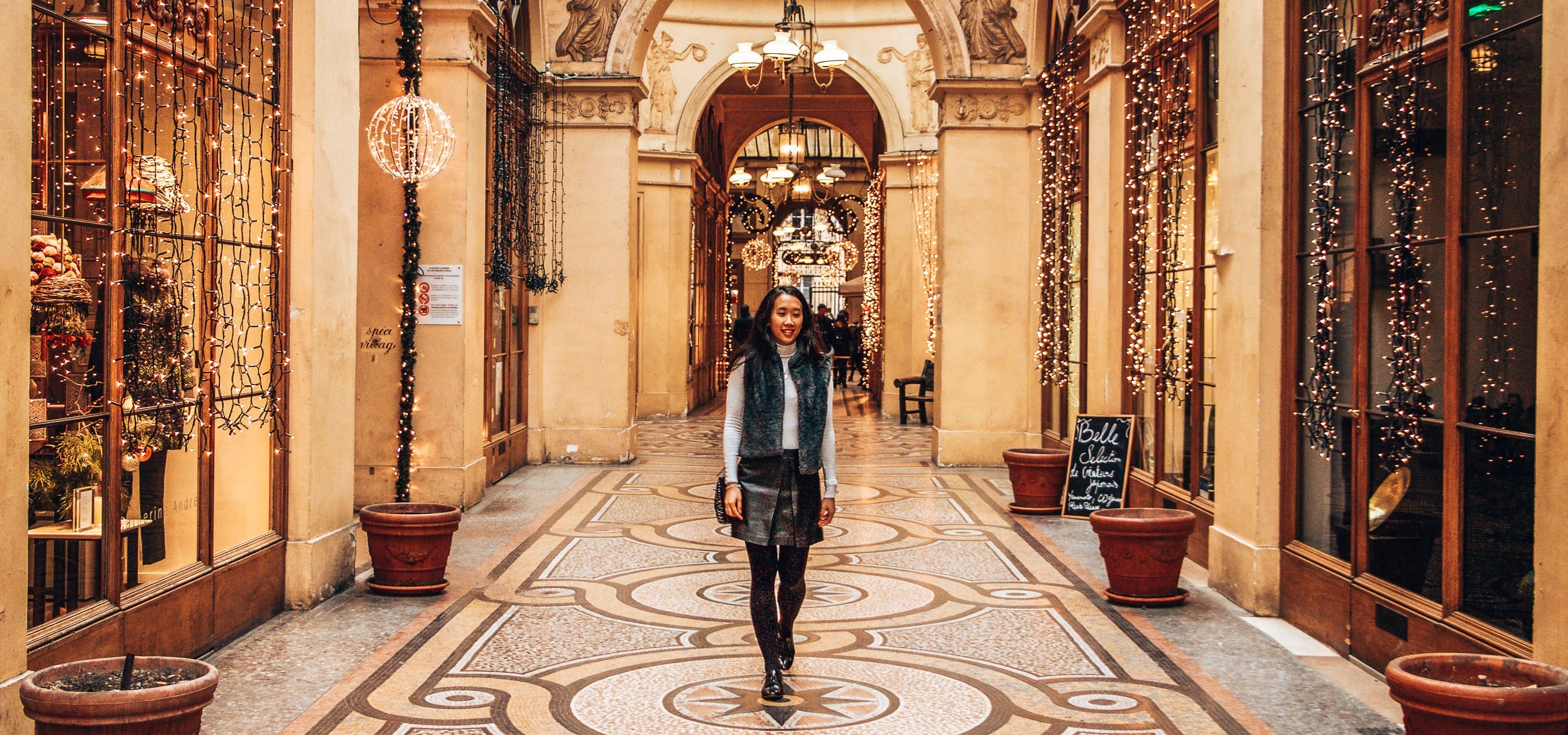 Jasmine walks through a mosaic corrider in Galerie Vivienne under fairylights, Paris