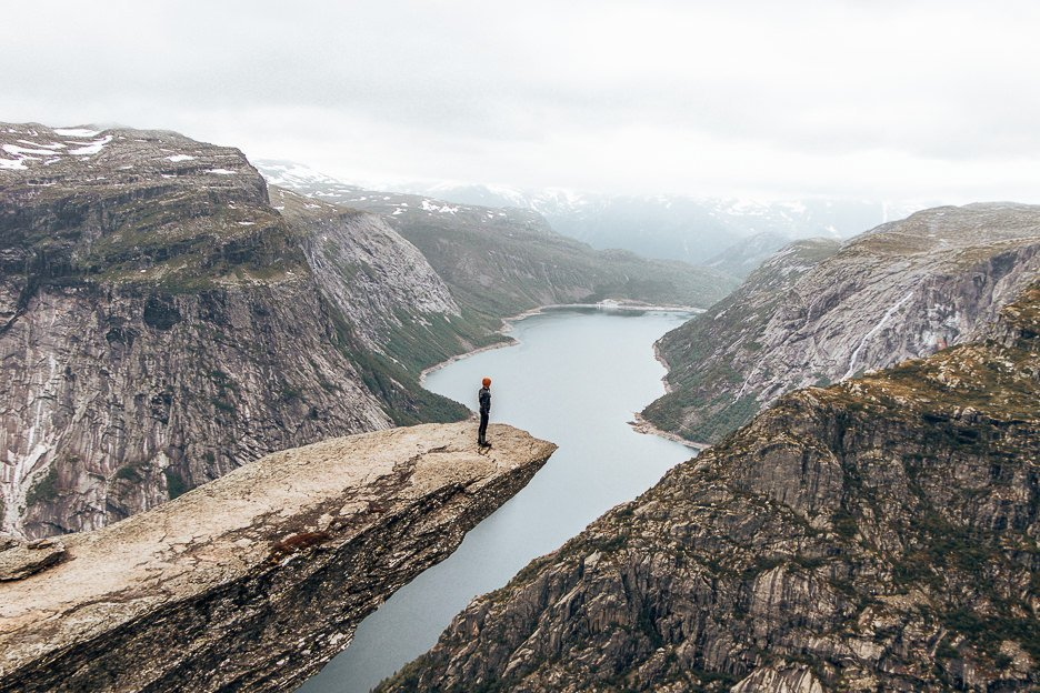 Jasmine stands on Trolltunga taking in the view over the fjord - Norway