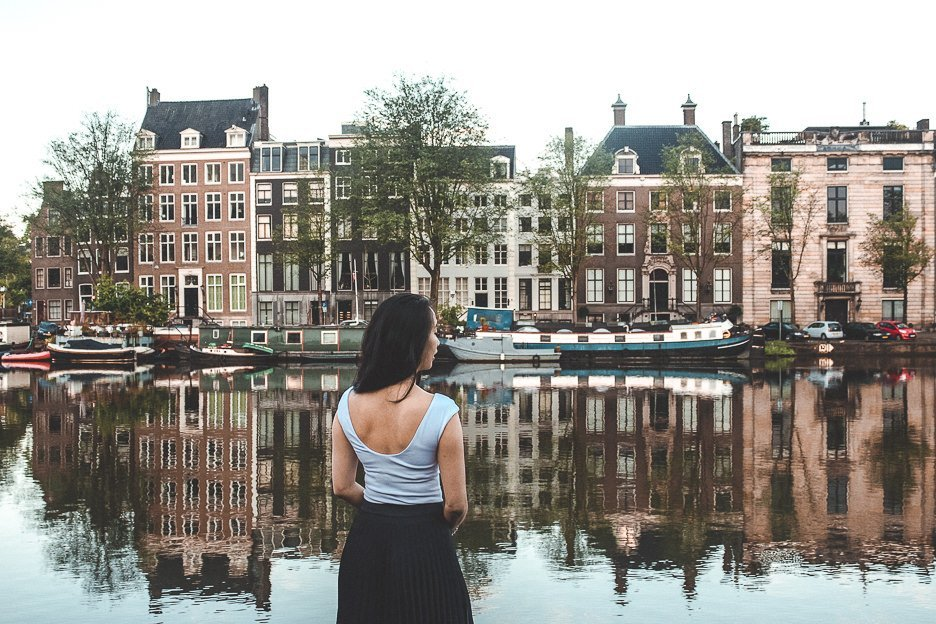A woman stands next to a canal in Amsterdam, the Netherlands