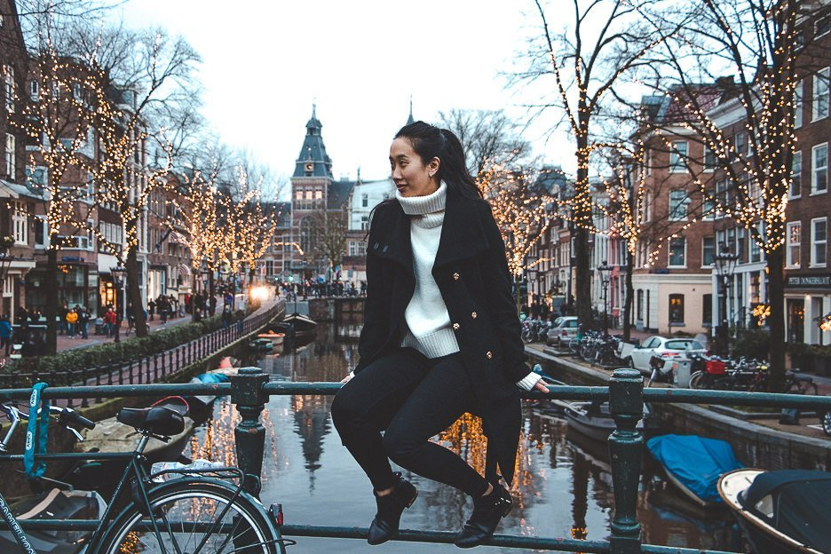 Sitting by the canals with fairylights in the background during winter in Amsterdam, The Netherlands