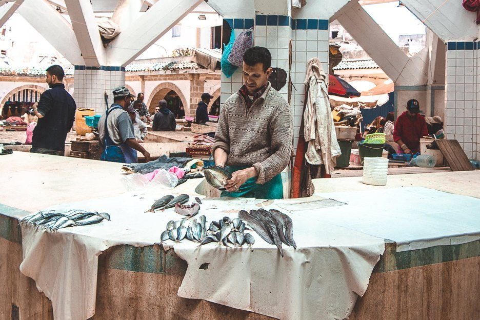 A man gutting fish at the Marche aux Poissons, Guide To Essaouira Morocco