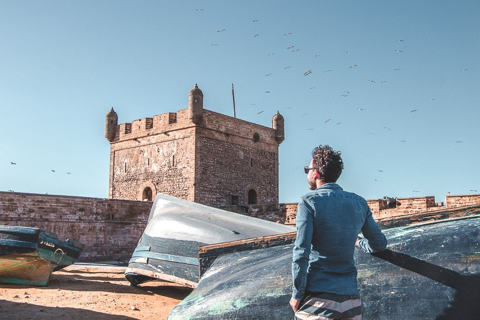 Bevan looking at Skala du Port from Port of Essaouira next to blue fishing boats Morocco