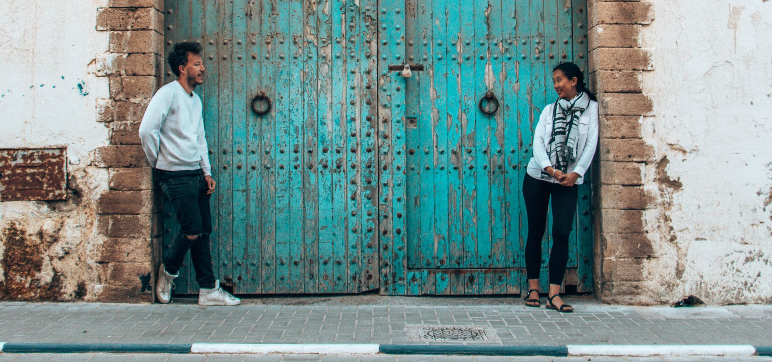 A couple pose in front of a blue door in Essaouira, Morocco