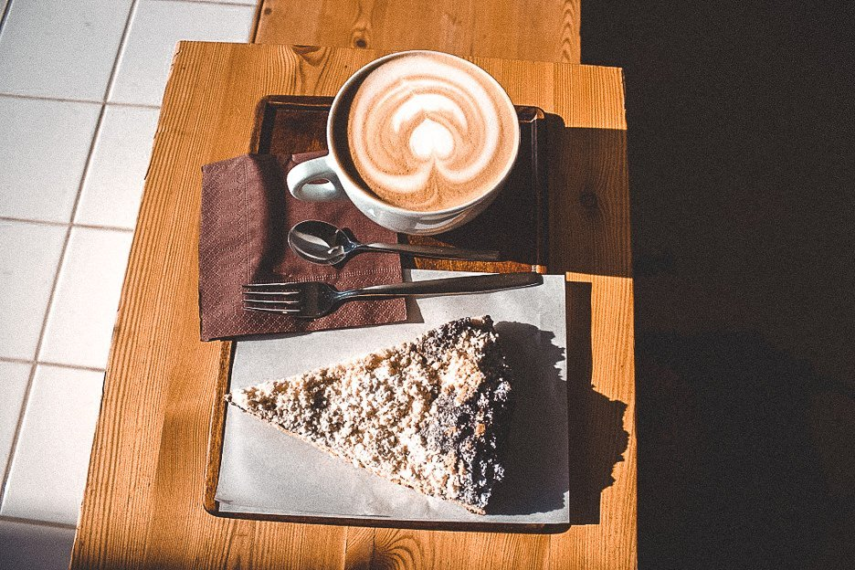A flat white and slice of pie on a table in the sunshine at EMA Espresso Bar, Prague, Czech Republic