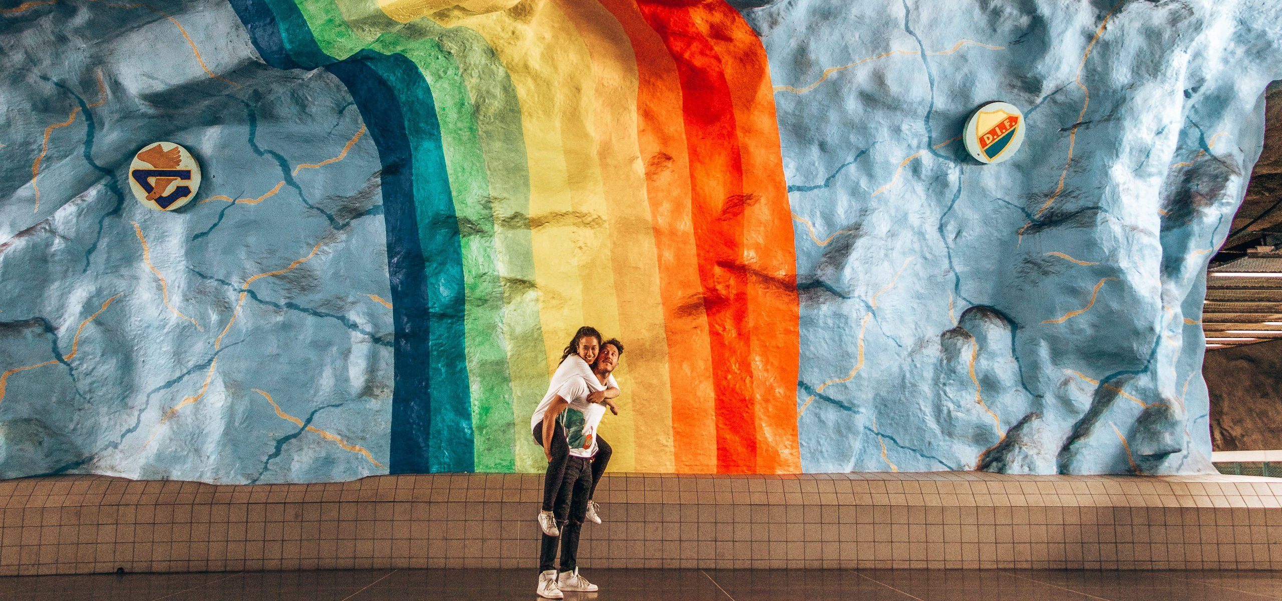 A couple stand under a rainbow in T-Centralen subway station, Stockholm itinerary 2 days