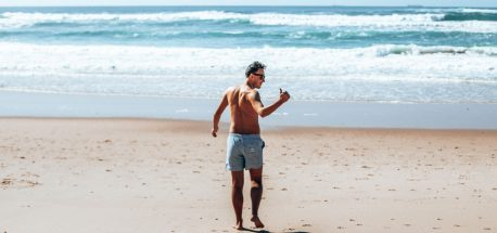 Bevan walks down to the beach wearing Eubi board shorts giving the thumbs up sign