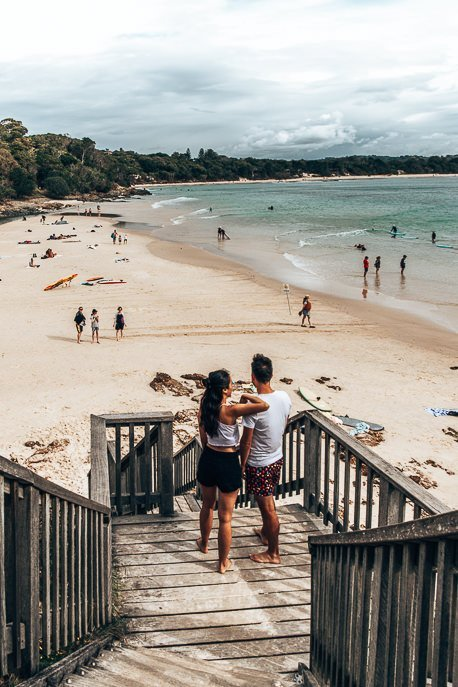 A couple watch swimmers and surfers from the Pass in Byron Bay