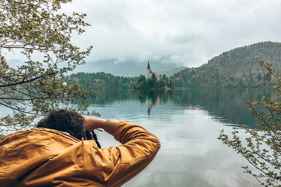 A man in a yellow jacket snaps a photo of Bled Castle on Bled Lake | Photography Camera Bag