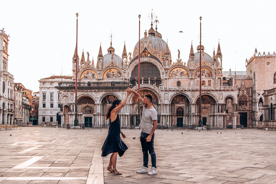 A man twirls a woman in front of St Mark's Basilica at sunrise  in Venice, Italy