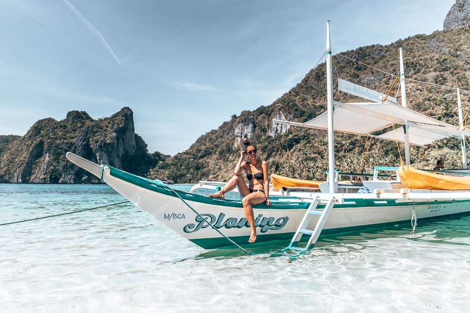 In Our Camera Bag | A girl sits on a Filipino boat during a boat tour in El Nido, The Philippines