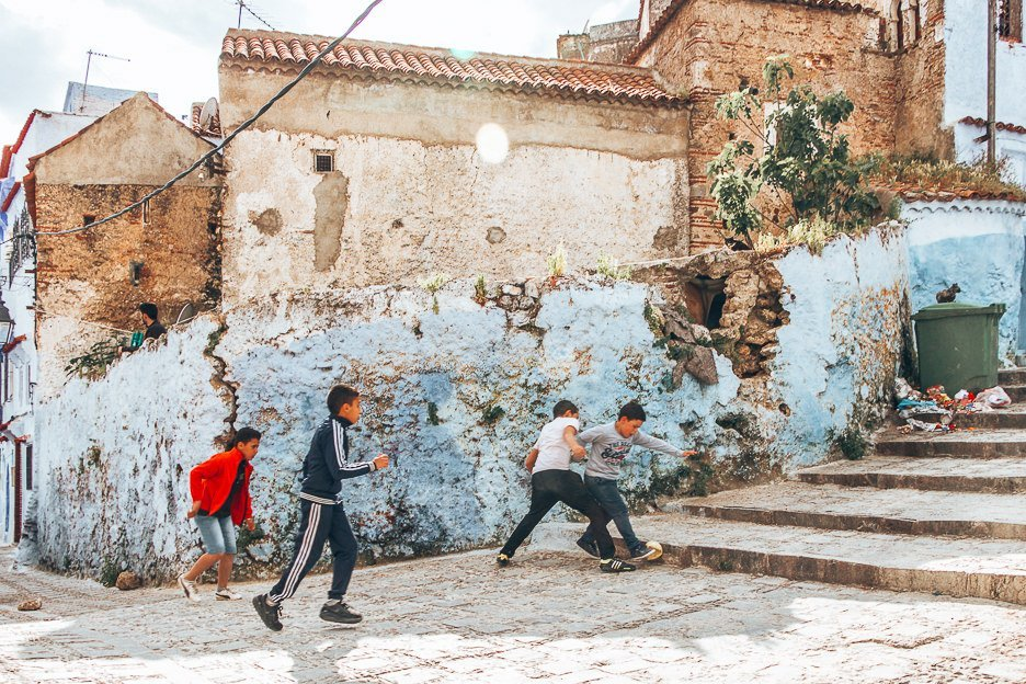 Young boys play football in the streets of Chefchaouen, Morocco