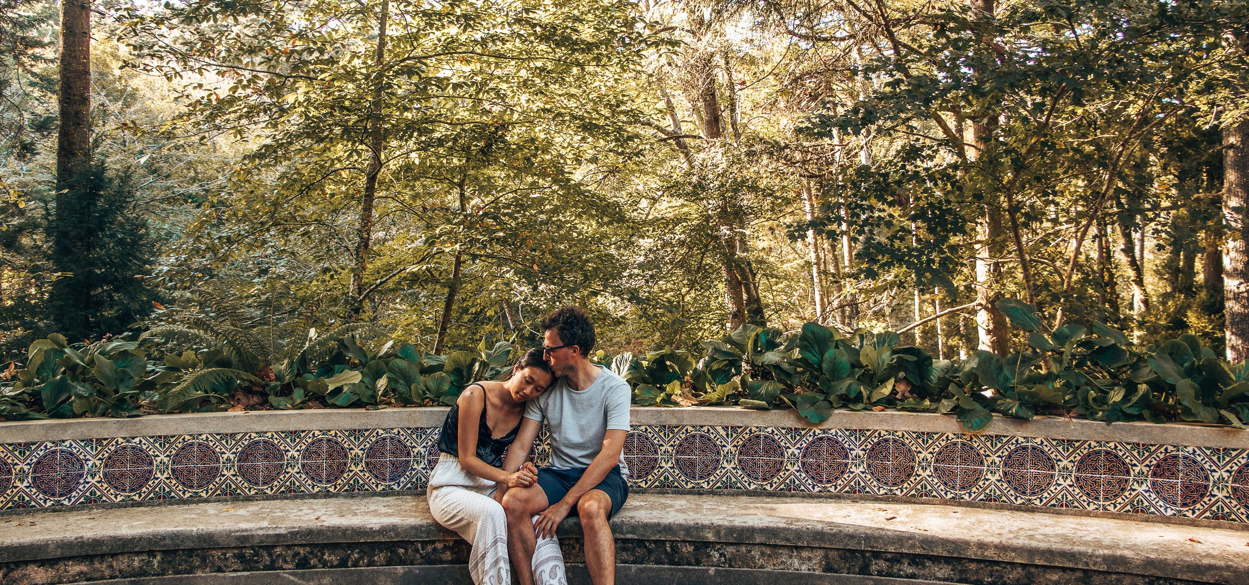 Travel rest days | A couple sit to rest on a mosaic bench in Sintra, Portgual