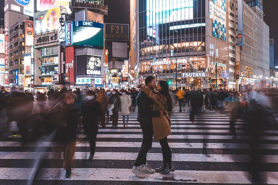 A man and woman share a kiss on the famous Shibuya Crossing in Tokyo, Japan
