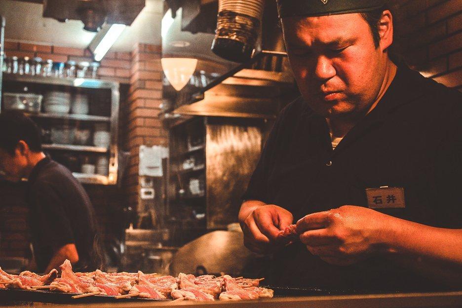 A stern faced man skewering yakitori chicken in Tokyo, Japan