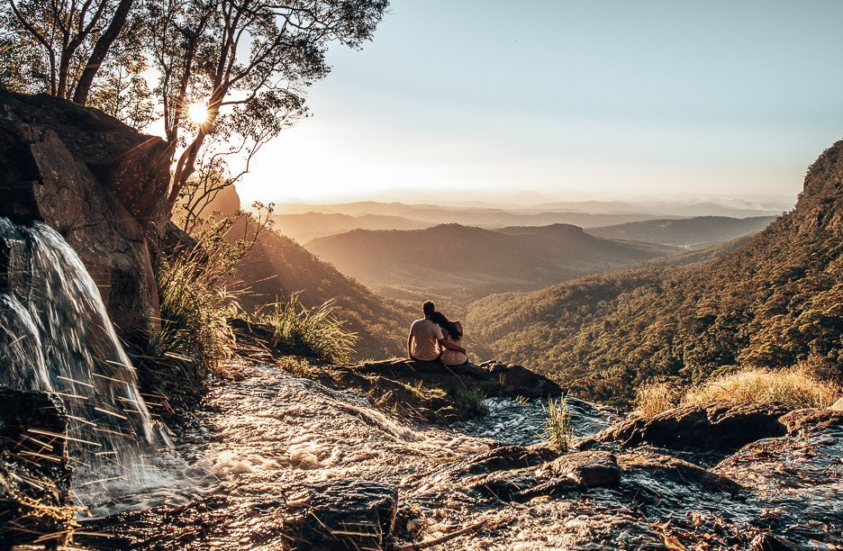 Couple watch the sunset at Moran Falls, Gold Coast, Queensland