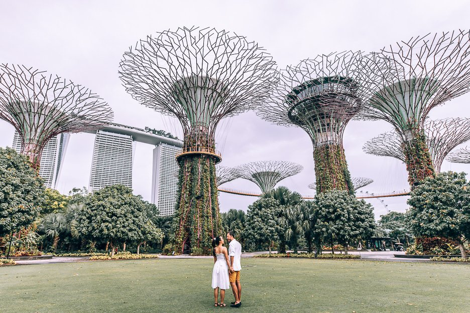 A couple stand on the lawn underneath the Supertree Grove at Gardens By The Bay, Singapore
