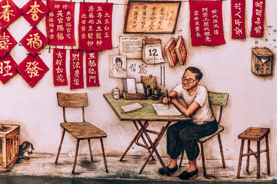 A mural of a man writing Chinese characters in Chinatown