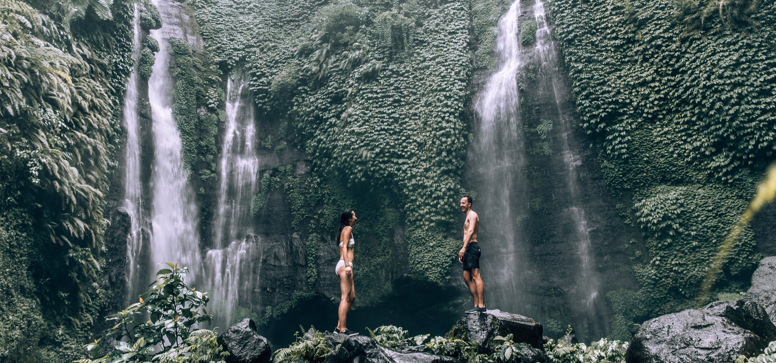 Best Free Travel Apps   A couple stand under Fiji Waterfalls in Bali, Indonesia